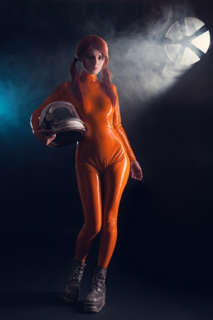 Sexy girl in latex catsuit holding helmet, sci-fi setting  Stock Photo