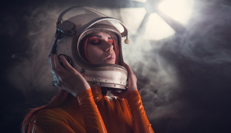 Portrait of astronaut girl in helmet, studio shot  Stock Photo