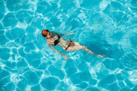 Young redhead woman in orange and black swimwear in swimming pool  photo