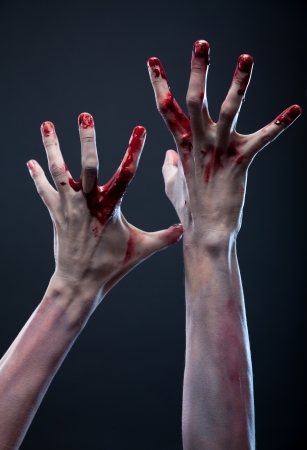 Bloody zombie hands, studio shot over gray background  Stock Photo