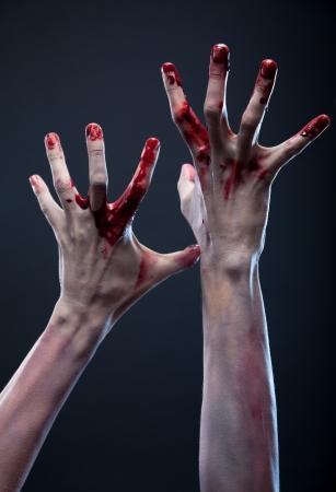 Bloody zombie hands, studio shot over gray background  Standard-Bild
