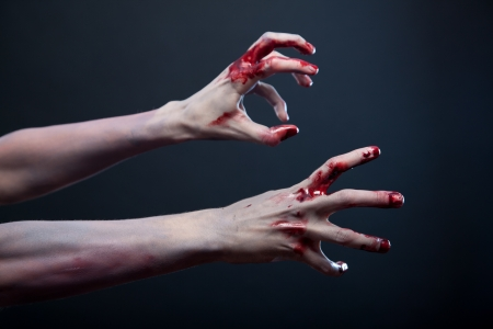 creepy monster: Zombie stretching his bloody hands, studio shot over gray background