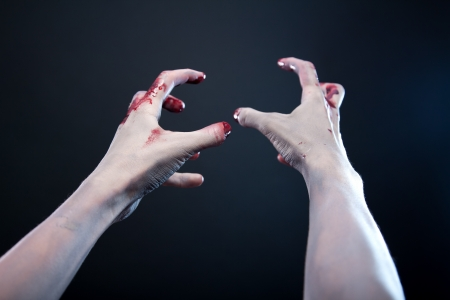 scary hand: Grey skin bloody zombie hands, studio shot over gray background  Stock Photo
