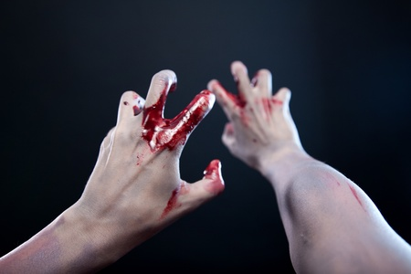Pale bloody zombie hands, studio shot over gray background  photo