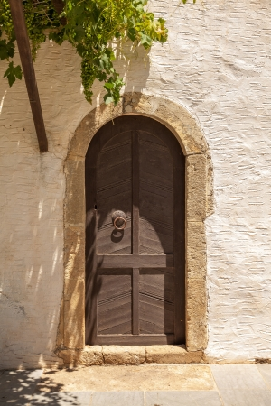 Antique wooden door with metal decor in monastery Touplu, Crete, Greece  photo