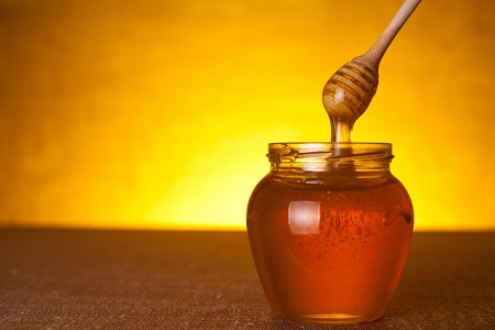 Honey jar with dipper and flowing honey   Stock Photo