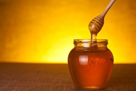 Honingpot met dipper en vloeiende honing