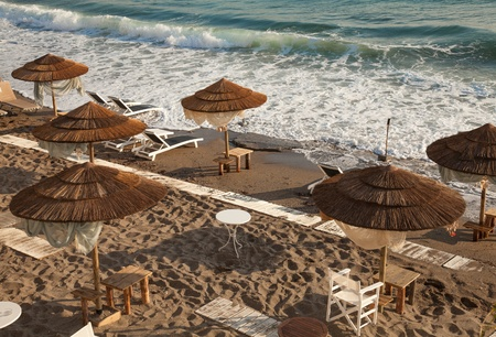 bliss: Beach with wooden umbrellas, Crete, Greece  Stock Photo