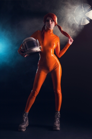 Sexy girl in orange latex catsuit holding helmet, sci-fi setting  Stock Photo