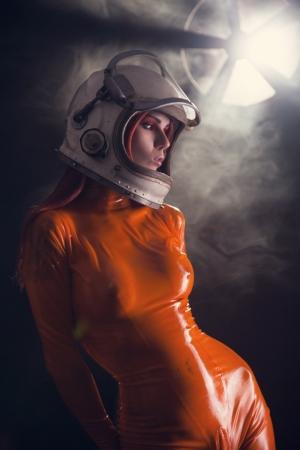 Portret van sexy meisje in oranje latex catsuit en ruimte helm, sci-fi omgeving Stockfoto