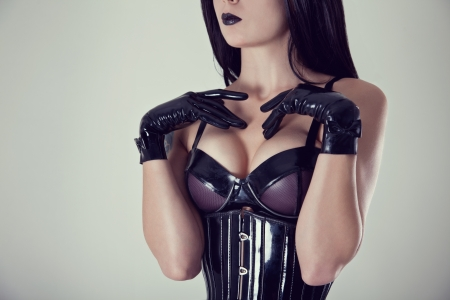 Close-up shot of female breasts in latex bra, studio shot   photo