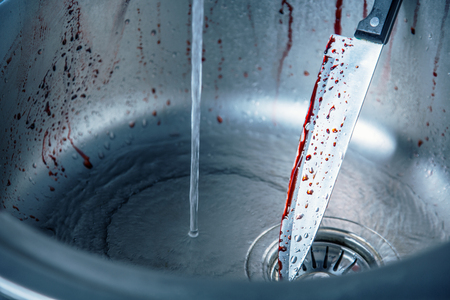 bloodstains: Cleaning bloody knife in kitchen sink, Halloween or crime scene  Stock Photo