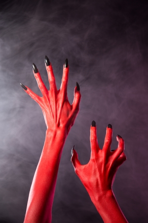 monster hand: Red devil hands with black nails, Halloween theme. Stock Photo