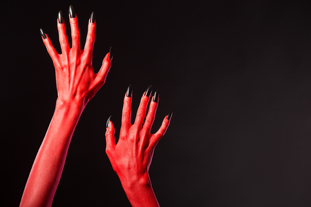diabolic: Red devil hands with black nails, Halloween theme. Stock Photo