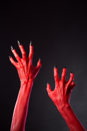 red devil: Red devil hands with black nails, Halloween theme. Stock Photo