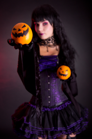 Beautiful witch in purple gothic Halloween costume with Jack lantern oranges, selective focus on fruits  photo