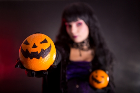 Pretty witch in purple Halloween costume with Jack lantern oranges, selective focus on fruits  photo