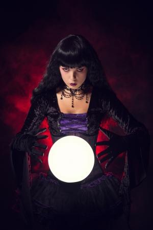Mooie heks of waarzegster met een kristallen bol, studio opname op rokerige achtergrond Stockfoto