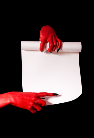 Red devil hands with black nails holding paper scroll and pointing at signature place   photo