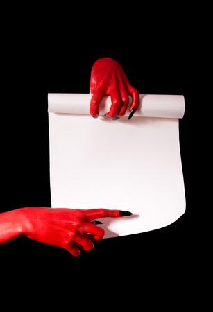 pacto: Red Devil manos con uñas negras sosteniendo rollo de papel y apuntando al lugar de la firma