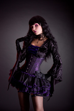 Beautiful witch in purple and black gothic Halloween outfit, studio shot  photo