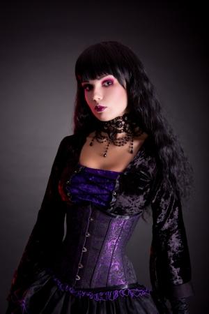ハロウィーンの衣装は、黒の背景で撮影スタジオを身に着けている美しいゴシック少女の肖像画