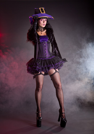 Pretty witch in purple and black gothic fantasy Halloween costume, full length shot   photo