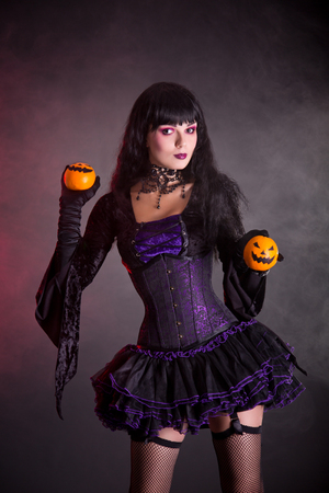 Smiling witch in purple gothic Halloween costume holding Jack-o-lantern style oranges  photo