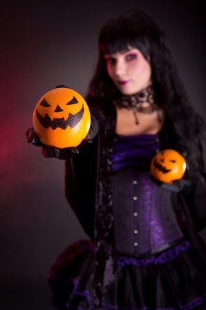 Beautiful witch holding Jack lantern oranges, selective focus on fruits  photo