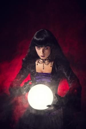 Prachtige gotische stijl waarzegster met een kristallen bol, studio opname op rokerige achtergrond