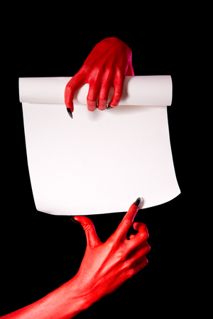 Red devil hands with paper scroll pointing at signature place, isolated on black  photo