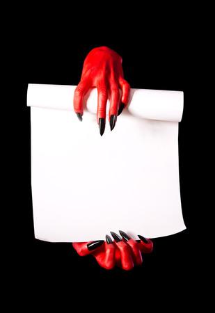 pacto: Red Devil tomados de la mano rollo de papel de acuerdo con el concepto del diablo, aislados en negro Foto de archivo