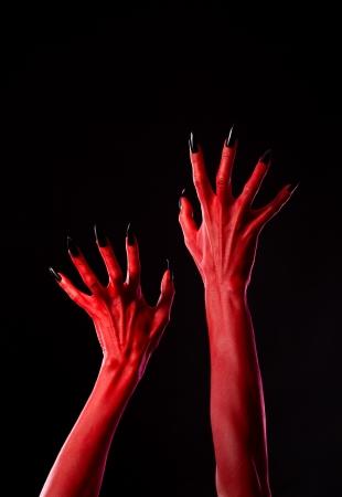 Spooky red demonic hands with black nails, Halloween theme, studio shot