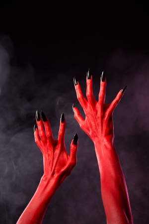underworld: Red devil hands with black sharp nails, Halloween theme, studio shot over smoky