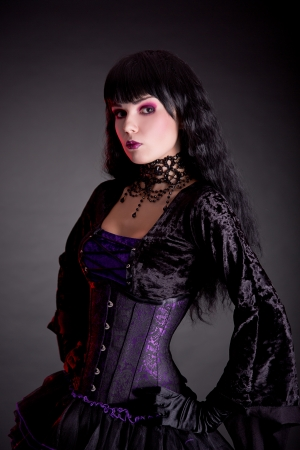 Portrait of attractive gothic girl in elegant medieval costume, studio shot isolated on black photo