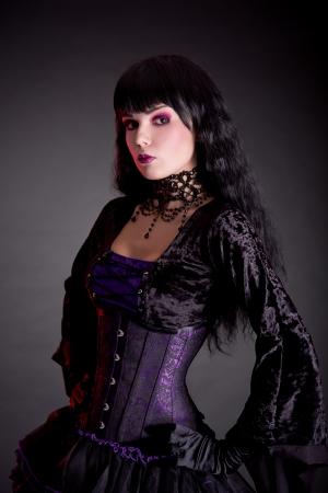 velvet dress: Portrait of attractive gothic girl in elegant medieval costume, studio shot isolated on black