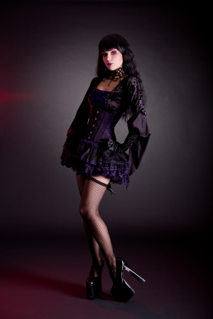 Pretty young woman in Victorian purple and black Halloween outfit and high heels   photo