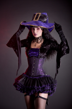 Smiling witch in purple and black gothic Halloween costume, studio shot isolated on black photo