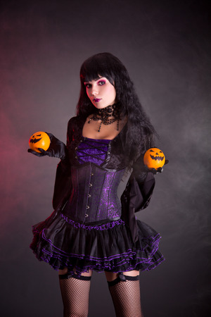 Pretty witch in purple Halloween costume holding Jack-o-lantern style oranges  photo