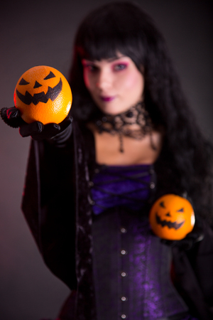 Pretty witch holding Jack o lantern oranges, selective focus on fruits  photo