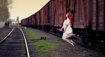 Redhead witch flying on the broom on train station  photo
