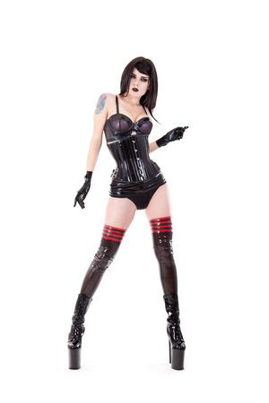 Sexy Domina in Latex-Outfit und High Heels, isoliert auf weiß