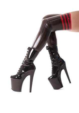 Piernas largas atractivas en medias de l�tex y botas de tac�n alto, aislado en blanco photo
