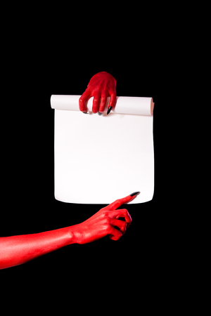 Red devil hands holding paper scroll and pointing at signature place, isolated on black background  photo