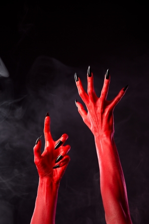diabolic: Spooky red devil hands with black nails on smoky background, studio shot  Stock Photo