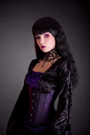 Portrait of beautiful gothic girl in Victorian style clothes, studio shot on black background  photo
