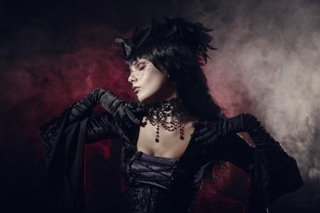 ビクトリア朝様式の服を着て、ロマンチックなゴシック様式女の子の煙のようなバック グラウンド上のショット