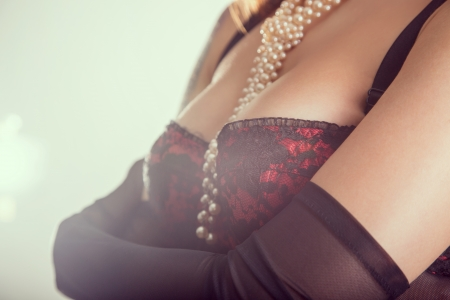 Close-up shot of a busty woman in vintage red bra and sheer gloves, studio shot