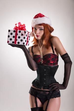 Mooi meisje draagt pinup outfit en Santa Claus hoed, bedrijf geschenk doos, kerst thema Stockfoto