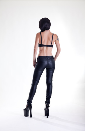 Rear view of young tattooed woman in leather pants and high heels, studio shot  photo